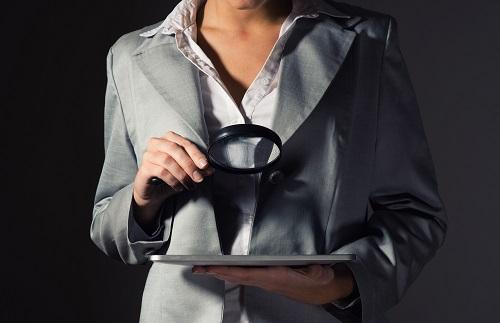 虫眼鏡で調査する女性